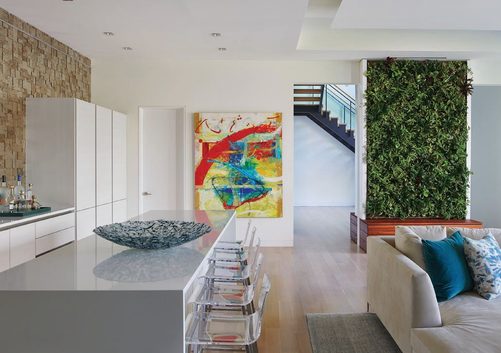 A natural wall of green and abstract art are standout design features of the home's lower level. PHOTOGRAPHED BY ANICE HOACHLANDER
